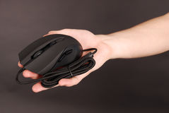 Man holds in his hand black computer optical mouse Royalty Free Stock Image
