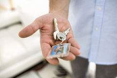 A man holds in his hand the keys of his house, indoor. Royalty Free Stock Photo
