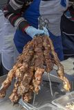 Man holds in his hand a lot of kebabs fried with meat. royalty free stock photography