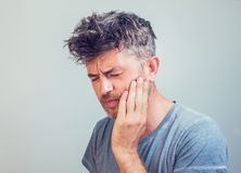 Man holds his hand near cheek toothache stock image
