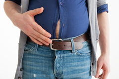 The man holds his hand over his swollen abdomen. To suffer from indigestion or gluttony royalty free stock images