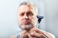 Man holds in his hand razor Royalty Free Stock Photos