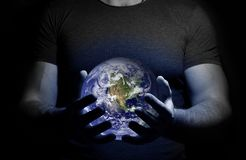 A man holds in his hands a glowing globe on a dark background. Close up