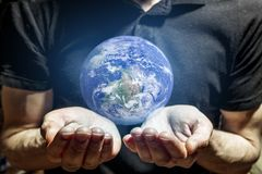 The man holds in his hands the glowing planet earth. The man holds carefully in his hands the glowing planet earth royalty free stock image