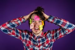 A man holds his hands on his head, stickers on his face. A man is shocked by his obligations and routine. Stickers with. Bank inscriptions, work, family Royalty Free Stock Image