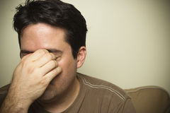 Man holds his nose in sinus pain. A man with a headache or sinus pain Royalty Free Stock Photography