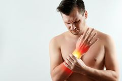 The man holds his wrist, the pain in his hand is highlighted in red, the tunnel syndrome. Light background. The concept of medicine, massage, physiotherapy royalty free stock image