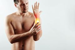 The man holds his wrist, the pain in his hand is highlighted in red, the tunnel syndrome. Light background. The concept of medicine, massage, physiotherapy stock image