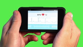 Man Holds Home Device to Record EKG. A man holds a handheld device or smartphone that monitors his EKG. Green screen, EKG and screen animation simulated stock footage