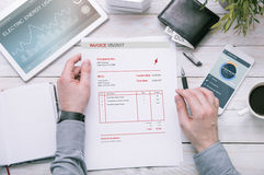 Man holds invoice of electric power usage over desk with tablet Royalty Free Stock Photo