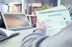 Man holds invoice. Of water usage Royalty Free Stock Photos