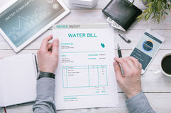 Man holds invoice of water usage over desk Stock Image