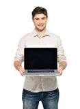 Man holds laptop with blank screen Royalty Free Stock Image