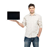Man holds laptop with blank screen Royalty Free Stock Photography