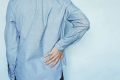 A man holds the liver. A man holds the liver on a blue background. Pain in the abdomen. Cirrhosis of the liver. Closeup. Tired businessman with back pain stock photos
