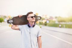 Man Holds Longboard. Handsome skateboarder dressed in grey t-shirt and sunglasses with earphones holds longboard on shoulder on city street Stock Images