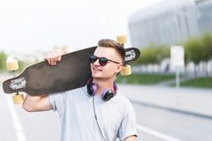 Man Holds Longboard. Skateboarder dressed in grey t-shirt and sunglasses with earphones holds longboard on shoulder on city street Stock Photography