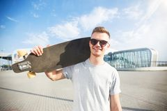 Man Holds Longboard. Skateboarder dressed in grey t-shirt and sunglasses holds longboard on shoulder before modern building Royalty Free Stock Images