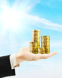 Man holds a lot of golden coins on his palm. Concept of wealth Stock Image