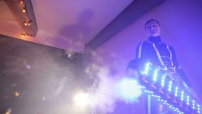 Man holds a machine for confetti. A shot by a confetti machine, a pipe sweeps the confetti and smoke. Man holds a machine for confetti. A shot by a confetti stock video footage