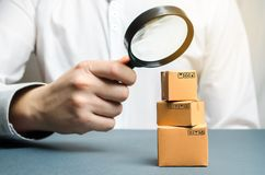 A man holds a magnifying glass above the boxes. Examination of goods for the presence of contraband, prohibited goods, defects. Quality control, authentication stock photo