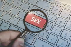 Man holds magnifying glass above the enter red key with the written word Sex on the computer keyboard background. Searching for sex dating in internet. Virtual stock photography
