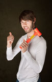 Man Holds Mallet. Confident bearded young man with mallet gives thumbs up Stock Photo