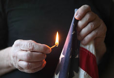Holding match to American flag Royalty Free Stock Photos