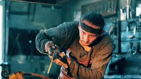 Man holds metal tongs while working with a knife at a forge. 4K stock footage