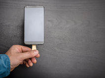 Man holds mobile phone on a stick like chocolate popsicle on a dark background Royalty Free Stock Image