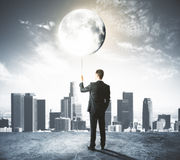 Man holds the Moon like a balloon at city background Royalty Free Stock Images
