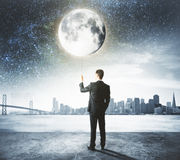 Man holds the moon like a balloon at city background Stock Photos