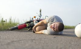 A man holds onto his knee, lying on the asphalt near the motorcycle, the theme of road accidents stock images