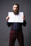 Man holds open journal. Handsome man with long beard hipster in shirt with suspenders holds open journal for copy space on grey background royalty free stock photo