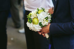 Man holds an original wedding bouquet made of white flowers and. Little apples Stock Photo