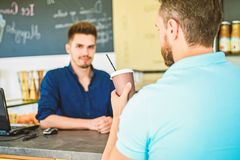 Man holds paper cup with coffee barista guy stand on background. Client got his drink. Have sip of energy. Man client stock photography
