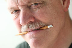 Man holds pencil in mouth Stock Photos
