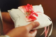 Man holds a pillow with wedding rings decorated with red and whi Royalty Free Stock Photo