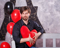 Man holds plush heart. Man holding big red plush heart. The concept for Valentine`s Day. Smoothie Stock Photos