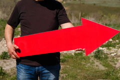 A man holds a red arrow pointer. Outdoor Stock Photos