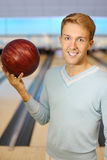 Man holds red ball in bowling club Royalty Free Stock Photos