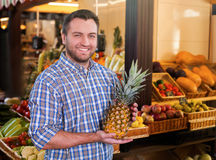 Man holds ripe pineapple in hands. Royalty Free Stock Image