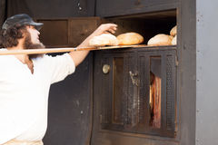 Man holds shovel on a loaf bread. Man with a beard is going to take out the bread out of the oven a wooden shovel royalty free stock photo