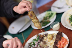 Man holds skewer of kebab Royalty Free Stock Photo