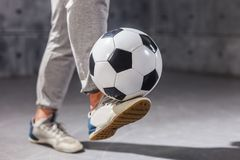 Man holds a soccer ball on his leg royalty free stock images