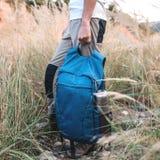 Man holds sport blue backpack stock image