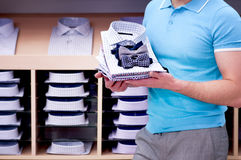 Man  holds stack of  shirt against showcase. Royalty Free Stock Photos