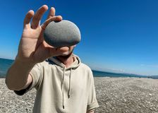 Man holds a stone in front of his face. A place for a label stock photos