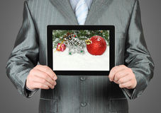 Man holds tablet PC with Christmas composition. On dark background Stock Image