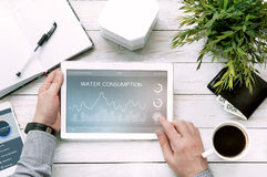 Man holds tablet pc with water usage application Stock Photo